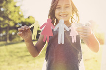 a girl child holding paper dolls