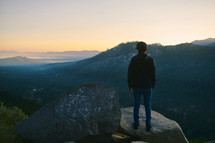 a man standing on a mountaintop looking out at the view