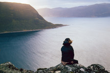 A person sitting on a high cliff overlooking a body of water surrounded by mountains.