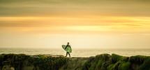 a surfer walking carrying a surfboard