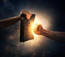 hand punching a Bible
