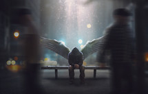 An angel sits on a bench as people pass by