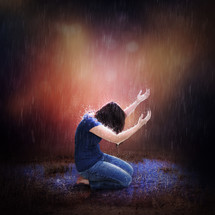woman kneeling praising God in the rain