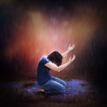 woman kneeling praising God in the rain