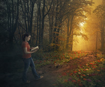 a girl walking along a forest trail lined by flowers reading a Bible