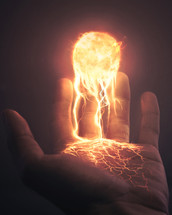 A hand holding the sun with burning streams of light and lava.