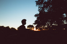 silhouette of a boy outdoors at dusk