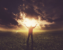 man standing with his arms raised in praise and worship to God under the glowing sun