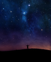 Silhouette of man with arms raised standing on a hill worshipping under the starry night sky.