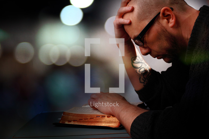 Man with bald head and tattoo praying with open bible