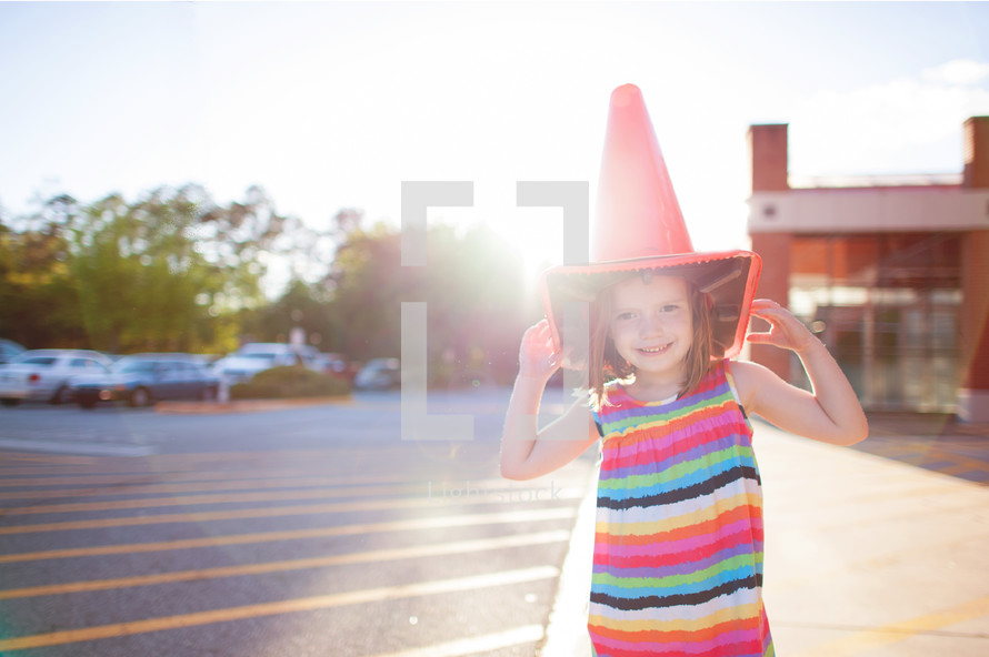 girl child acting silly with a traffic cone on her head
