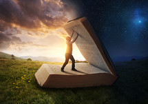 A man holding open a giant Bible between day and night.