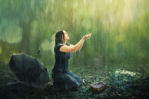 a woman kneeling in rain