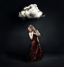 A woman in a red dress standing under a tiny cloud with rain drops.