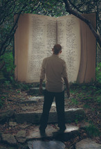 man standing in front of a giant Bible in a forest