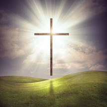 A large glowing cross over a grassy field with bright glowing lights.