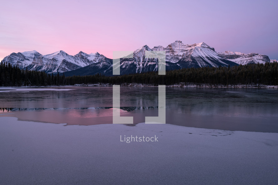 snow capped mountains and icy lake at sunset