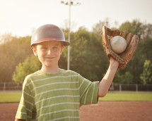 a child with a ball in his glove