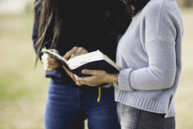 young women reading a Bible together