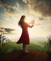 Woman standing on a hill reading the Bible with rays of light beaming from the clouds.