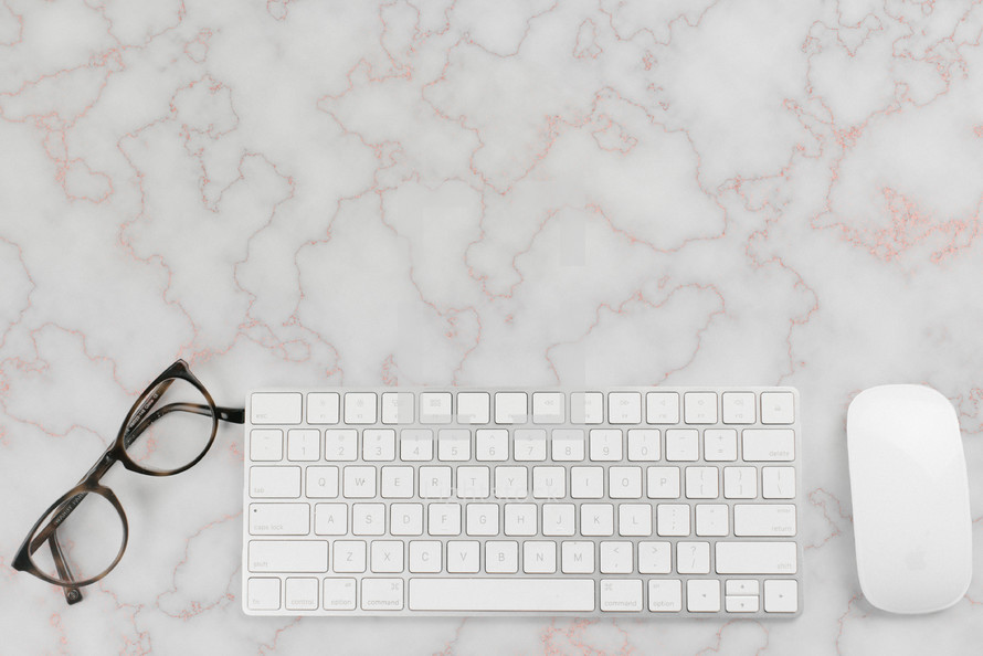 reading glasses, computer keyboard and computer mouse on a desk