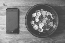 Coins in a bowl and a cell phone on a wooden table.
