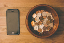 bowl of coins and an iPhone
