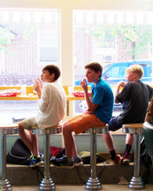 Soda Fountain Kids - A group of three young elementary school boys sit and relax together in a local soda fountain after school eating French fries, hamburgers and soda on a sunny day sitting on round stools in front of a large picture window in a local downtown soda shop restaurant.