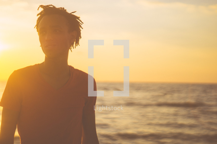African-American man standing on a beach at sunset