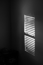 sunlight through cracks in blinds on a window