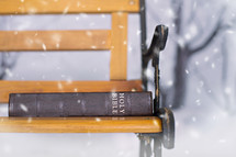 a Bible sitting on a park bench in the snow