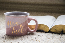 Mom Fuel coffee mug and open Bible