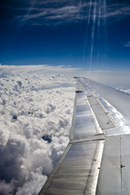 commercial airplane wing over the clouds
