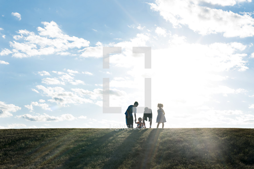 children standing on a hill outdoors