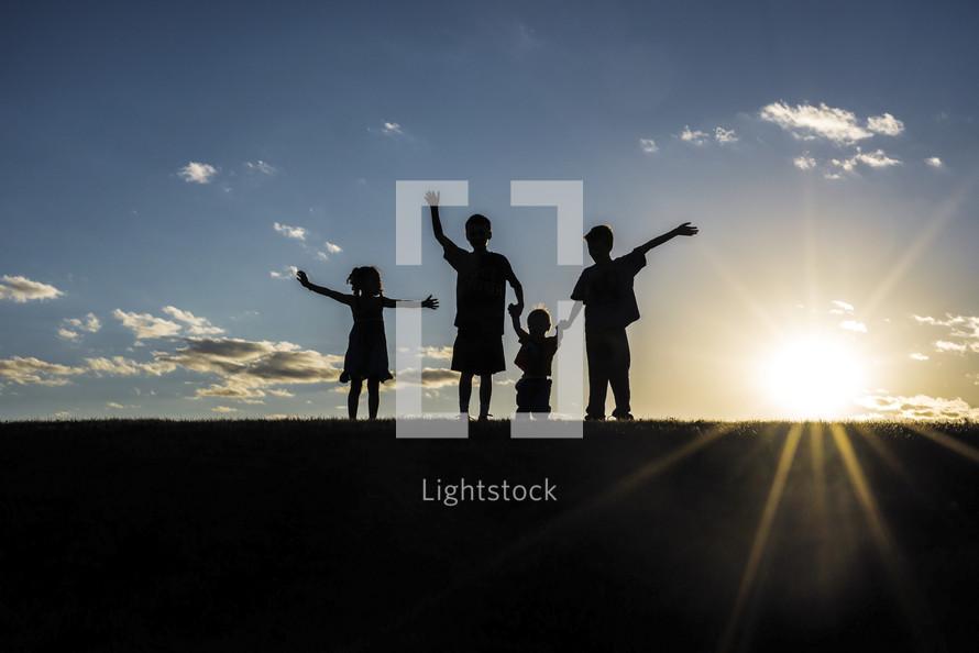 silhouettes of children waving