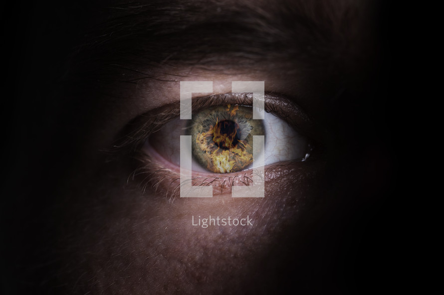 person's eye with reflections of fire and flames.