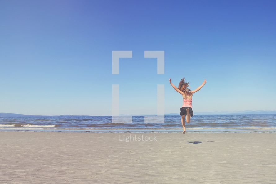 a young girl leaps towards water