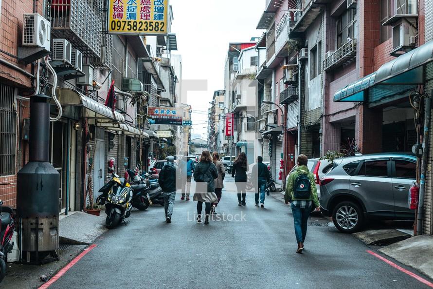 people walking on a narrow street in Taiwan