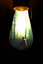 view of a boy sitting in a forest in a lightbulb