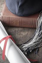 graduation cap, diploma, and Bible