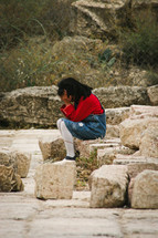 a little girl crying sitting on rocks