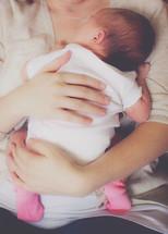 mother snuggling her infant daughter