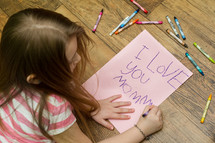 little girl coloring an I love you mommy card