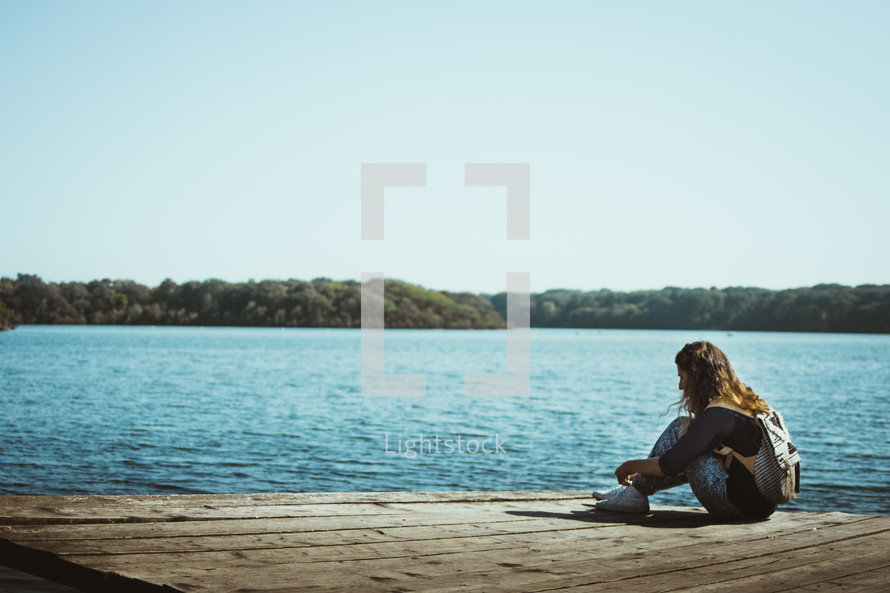 a young woman sitting alone on a dock