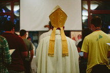 priest walking down the aisle at a worship service