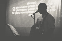 silhouette of a man singing into a microphone and lyrics on a projection screen