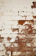 white pealing paint on a red brick wall