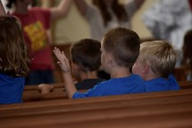 kids with raised hands sitting in church pews singing songs at VBS