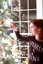 a child hanging an ornament on a Christmas tree