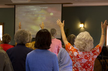 women with raised hands at a worship service
